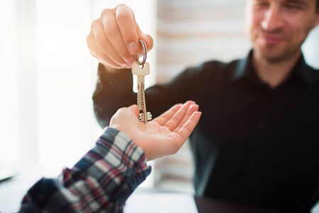 Real estate agent giving key of new house to young woman in office Zdjęcie Seryjne