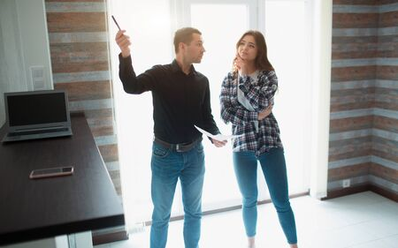 Realtor, broker or landlord shows an apartment to a young woman. She is going to sign a lease agreement with him.