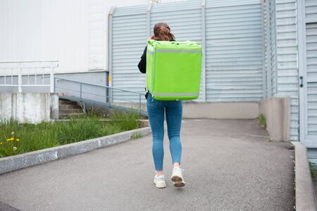 Food delivery concept. The food delivery woman has a green fridge backpack. She wants to deliver faster and get to customers. She stands with her back to the camera and a green large refrigerator backpack is clearly visible.