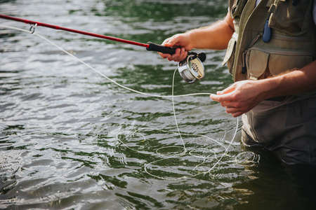 Young fisherman fishing on lake or river. Cut view of guy's hands holding fishing line. Preparing to catch some river or lake fish. Man stand in fresh water Banco de Imagens