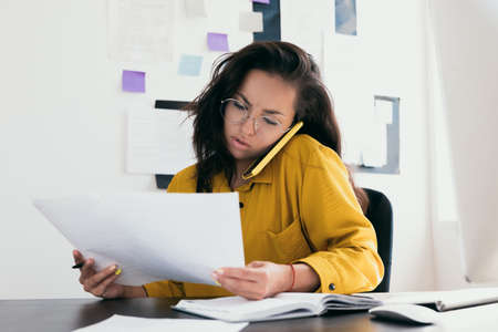 Confused young woman reading documents and discussing on the phone. Startup bussines concept. Woman in yellow clothes and in round eyewear talking by her phone. Work in office or from home.