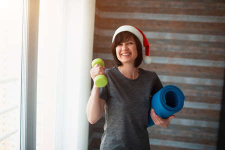 Adult fit slim woman has workout at home. Cheerful adult senior female person during christmas time or new year period. Holding one dumbbell and yoga mat in hands. Take care about body shape.
