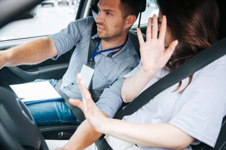Male driving instructor holds steering wheel and try to avoid a car accident. Young woman raised her hands. Safety driving a car concept. Fastened seat belts. Obtaining a drivers license concept. Banco de Imagens