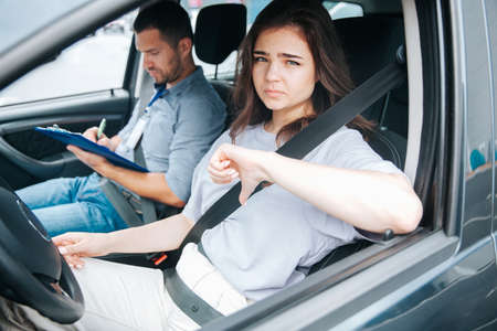 Sad female student fails her driving test and shows thumbs down. Attractive woman sits behind the wheel of a car and looks out the side window. Male instructor on front passenger seat takes notes.