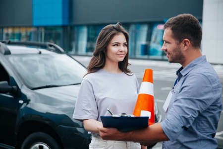 Female student of driving school signs instructors papers and looks at him with interest. Orange traffic cones with white stripe. Driving lessons. Obtaining a drivers license concept.