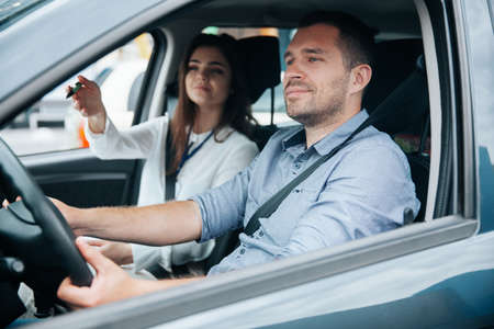 Female driving instructor pointing at object on road by her hand. Diligent male student driving the car and listening what his instructor is saying. Two people in car. Driving lessons concept.