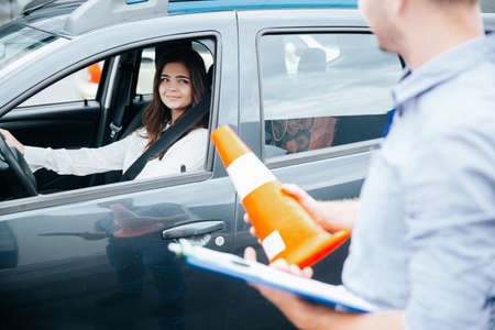 Attractive brunette woman on drivers seat with fastened seat belt smiles to male driving instructor with clipboard and orange traffic cone in his hands. Improving driving skills concept.