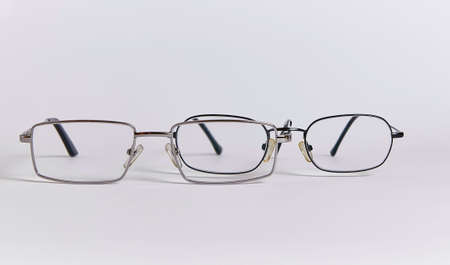 Two pairs of glasses are arranged one after another, like two people. Glasses close-up isolated on a white background