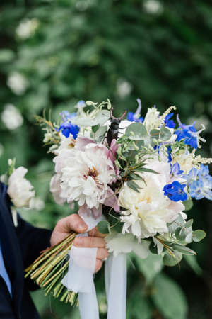The groom holding a wedding bouquet of peonies on which stag beetle sitting