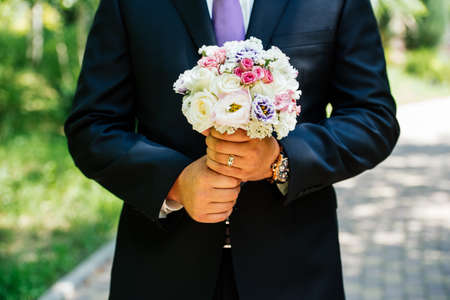 Wedding bouquet of white, pink and purple roses in the grooms hands Stock Photo
