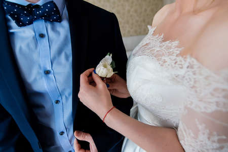 fastens: Bride fastens groom boutonniere to buttonhole Stock Photo