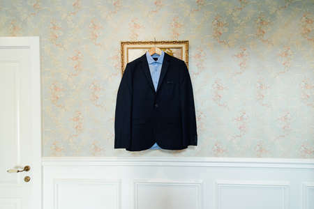 cuff: Blue shirt and black jacket on trempel on the wall with a floral pattern near white door. Groom wear