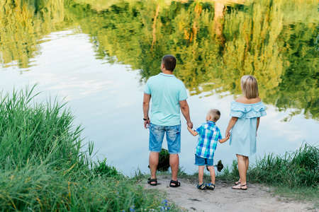three generations of women: Mother, father and son holding hands on the river bank. Happy young family spending time on the bank of the river on a warm summer day Stock Photo