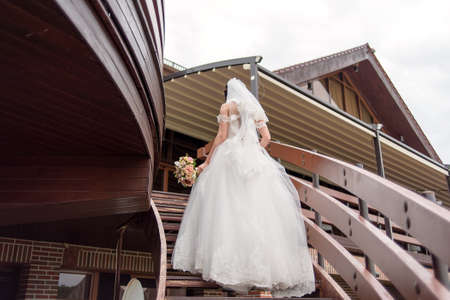 bajando escaleras: Bride in white wedding dress with bouquet in hand climbs the stairs