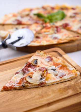 Pizza with mushrooms and sausages on a wooden board