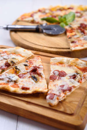 Pizza with mushrooms and hunting sausages on a wooden board Stock Photo