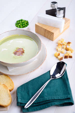 Pea cream soup with bacon in a white plate with toast. Green peas in a plate on a white table. Lunch at the restaurant.
