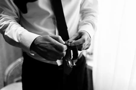 cuff link: The watch is in the hands of a man. Mens watches on the arm. Mens hands with a watch. Black and white photo Stock Photo