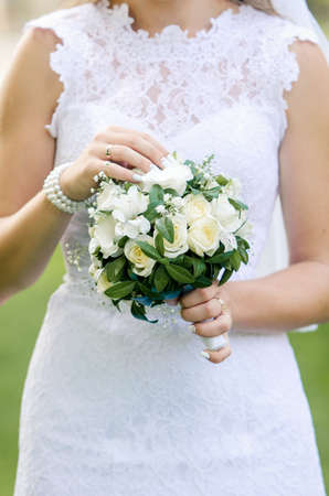 arm bouquet: Wedding bouquet of white flowers and greenery in the hands of the bride in a white dress