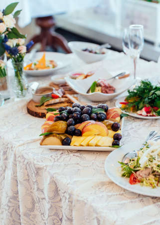 Plate with fruits on the dinner table. Grapes and pieces of apples and pears in a white plate on the table Stock Photo