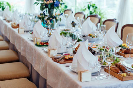 ware: Table setting. Table served for wedding banquet, close up view. White napkin on a white empty plate on a dining table Stock Photo