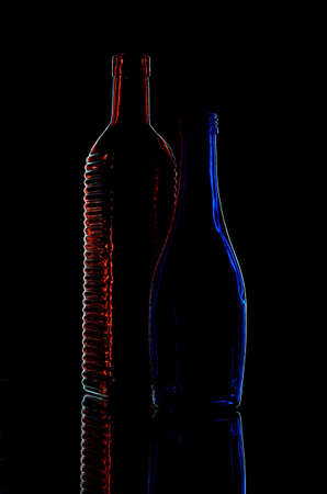 Elegant  red and blue glass wine bottles on a black background Stock Photo