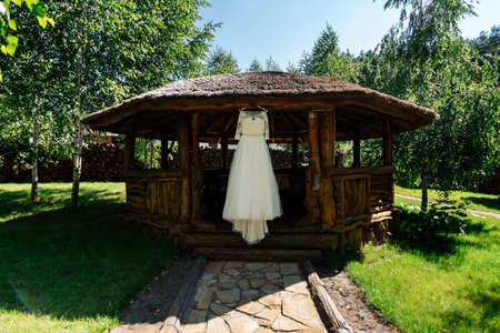Beautiful wedding dress hanging on the wooden arbor next to the birch outdoors Stock Photo