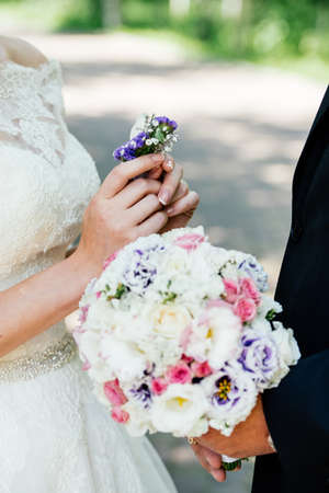 Boutonniere of white and purple flowers in the  brides hands