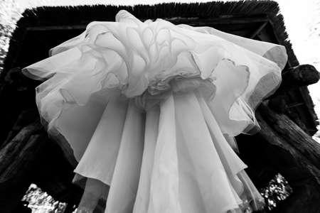 Bottom view of wedding dress hanging on the arbor. Abstract overhang wedding dress Stock Photo