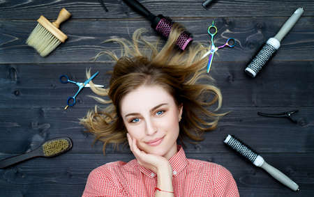 Happy smiling young woman in plaid shirt with hand on her chin and hairdresser tools among her. Top view 版權商用圖片