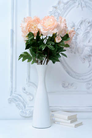 Artificial Pink Peonies In A White Vase Next To White Books Stock
