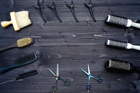 Hairdresser tools on wooden background. Top view on wooden table with scissors, comb, hairbrushes and hairclips, free space Stock Photo