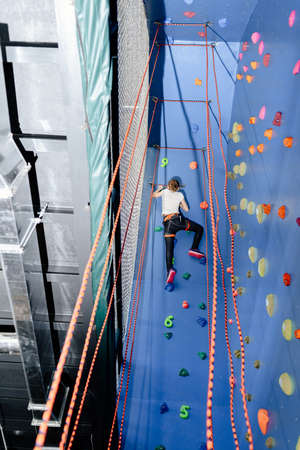Little girl climbing a rock climbing wall indoor. Back view of girl practicing climbing skills Stock Photo