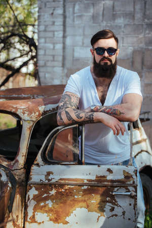 rusty car: Brutal bearded man with tattoo  in sunglasses and  jeans and white tee-shirt standing near the old car