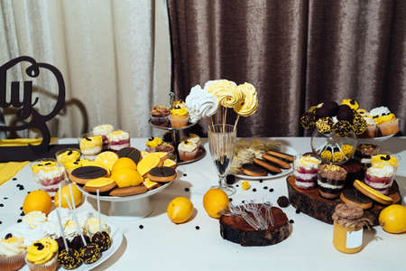 Holiday candy bar in yellow and brown color. Wedding candy bar served with cupcakes, cake pops, desserts in glasses, lemons and coffee beans