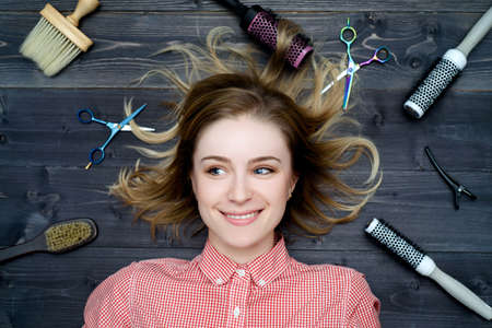 haircutting: Beautiful young smiling woman in plaid shirt with hairdresser tools among her looking away. Top view