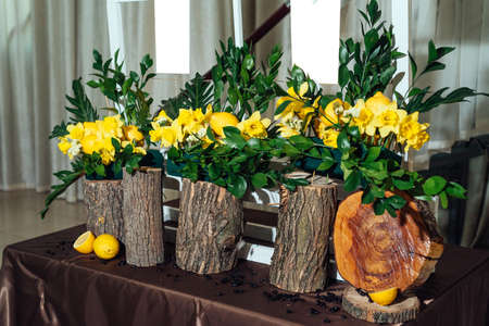 Wedding flower arrangements of yellow daffodils, greenery and lemons on stumps under seating plan for wedding reception guests list, close-up