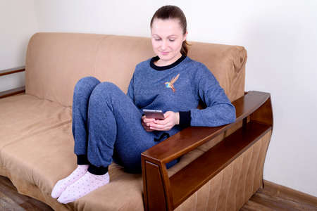 woman on phone: Beautiful young woman sitting on a sofa, using a smartphone and texting. Relaxing on the couch at home. Technology and communication concept