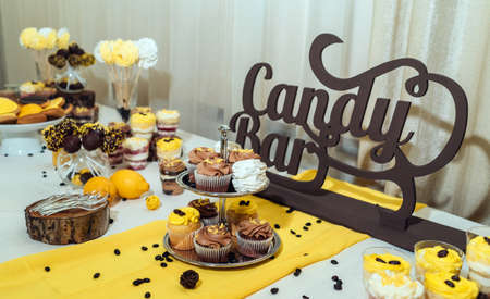 Holiday candy bar. Candy bar served with cupcakes with chocolate and lemon cream on stump and others sweets