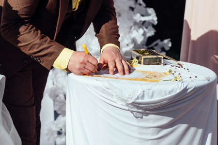 Groom make the signature. Bride and groom signing marriage license or wedding contract at the wedding ceremony