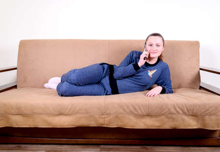 woman on phone: Beautiful young woman talking on the phone at home lying on the couch. Relaxing on the couch at home. Technology and communication concept