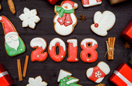 Happy new year 2018 sign symbol with red and white gingerbread cookies on dark wooden background, copy space. Top view, flat lay. Christmas cookies, santa, snowman, snowflake, cinnamon. free space Stock Photo