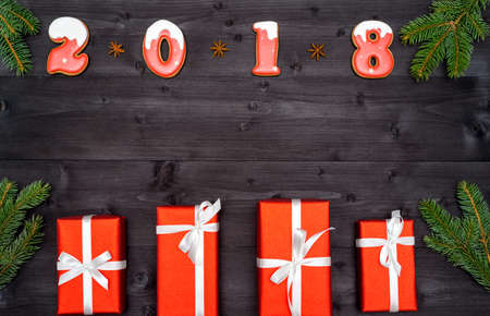Happy new year 2018 sign symbol from red and white gingerbread cookies on dark wooden background with red gift boxes, copy space. Top view, flat lay. New Year or Christmas background