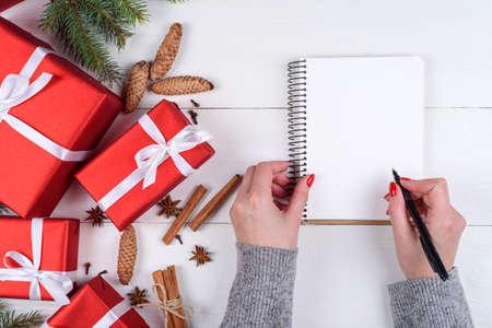 Draufsicht des Weihnachtshintergrundes mit den leeren leeren Tagebuch- und Mädchenhänden mit Stiftschreibenszielen auf weißem hölzernem Hintergrund, freier Raum. Flache Lage, Draufsicht