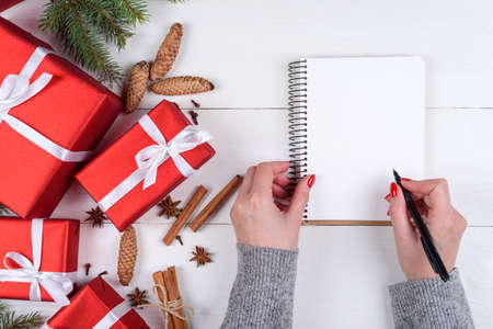 Top view of Christmas background with blank empty diary and girls hands with pen writing goals on white wooden background, free space. Flat lay, top view