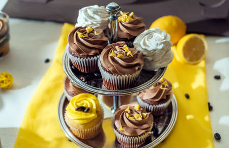 Holiday candy bar. Candy bar served with cupcakes with chocolate and lemon cream on metal stand Stock Photo