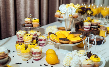 Holiday candy bar in yellow and brown color, selective focus. Wedding candy bar served with lemon biscuits, desserts in glasses, cupcakes, meringues,  lemons and coffee beans  Stock Photo
