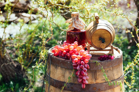 Old wooden wine barrel with bottle of wine and grapes on it. Wedding decorations outdoors Stockfoto