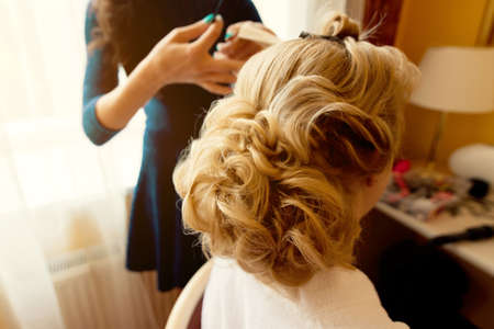 Hairdresser makes hairstyle for the bride. Bride morning