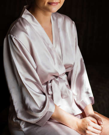 Beautiful young girl in silk robe sitting on chair and crosses her hands